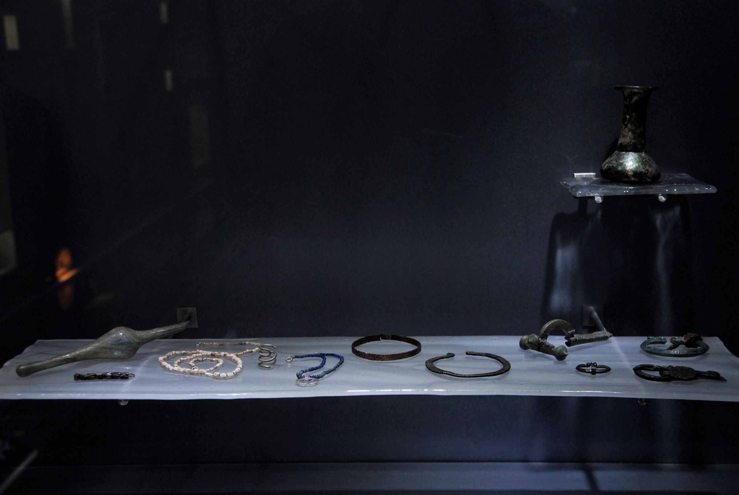 Jewelry and personal items in the display case with antique material